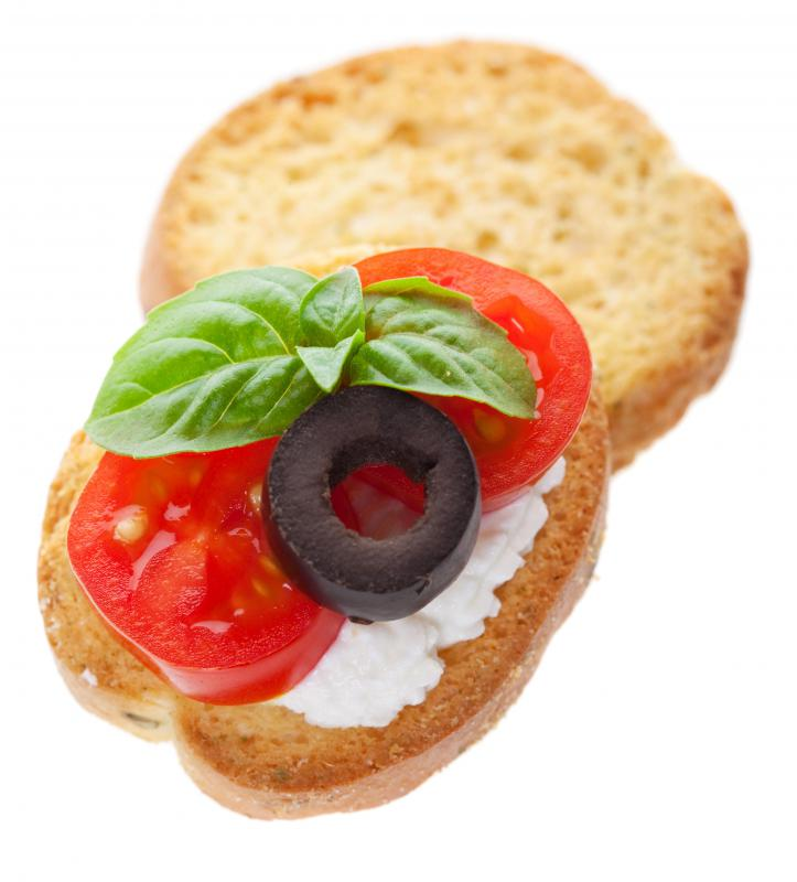 An appetizer with cream cheese, tomato, olive, and basil.
