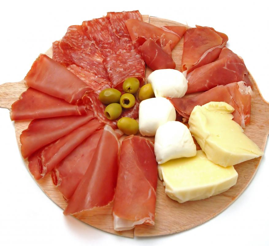 Classic antipasto platter including sliced parma ham and salami along with olives and assorted varieties of cheese.