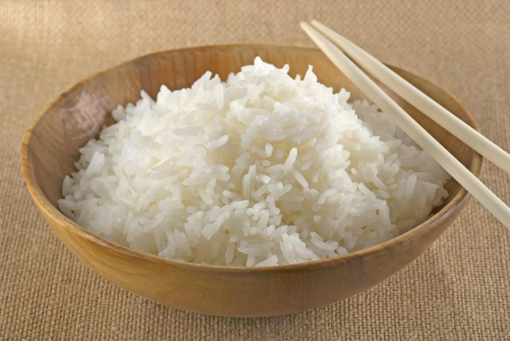 Cooked jasmine rice in a bowl with chopsticks.