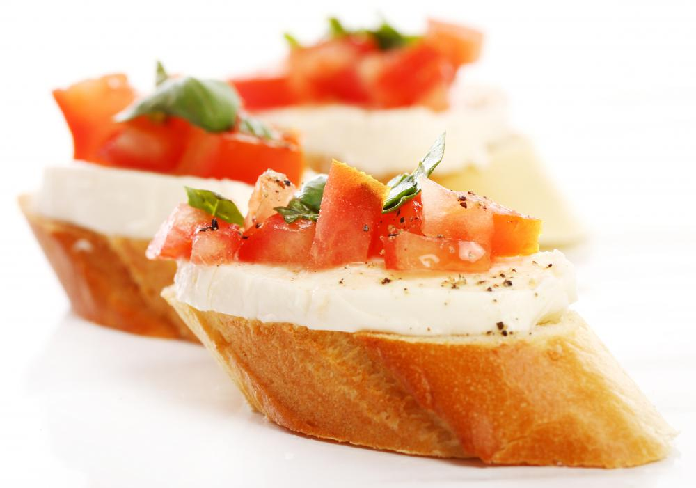 Crostini with mozzarella cheese, chopped tomato and basil.
