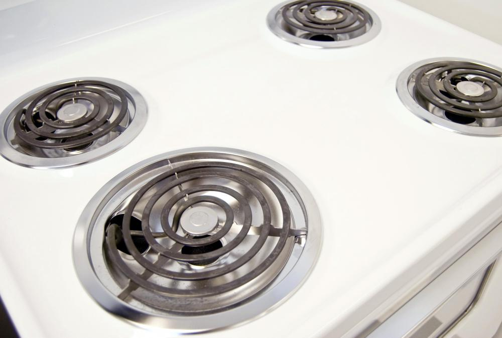 Each burner on an electric stove features a drip pan.
