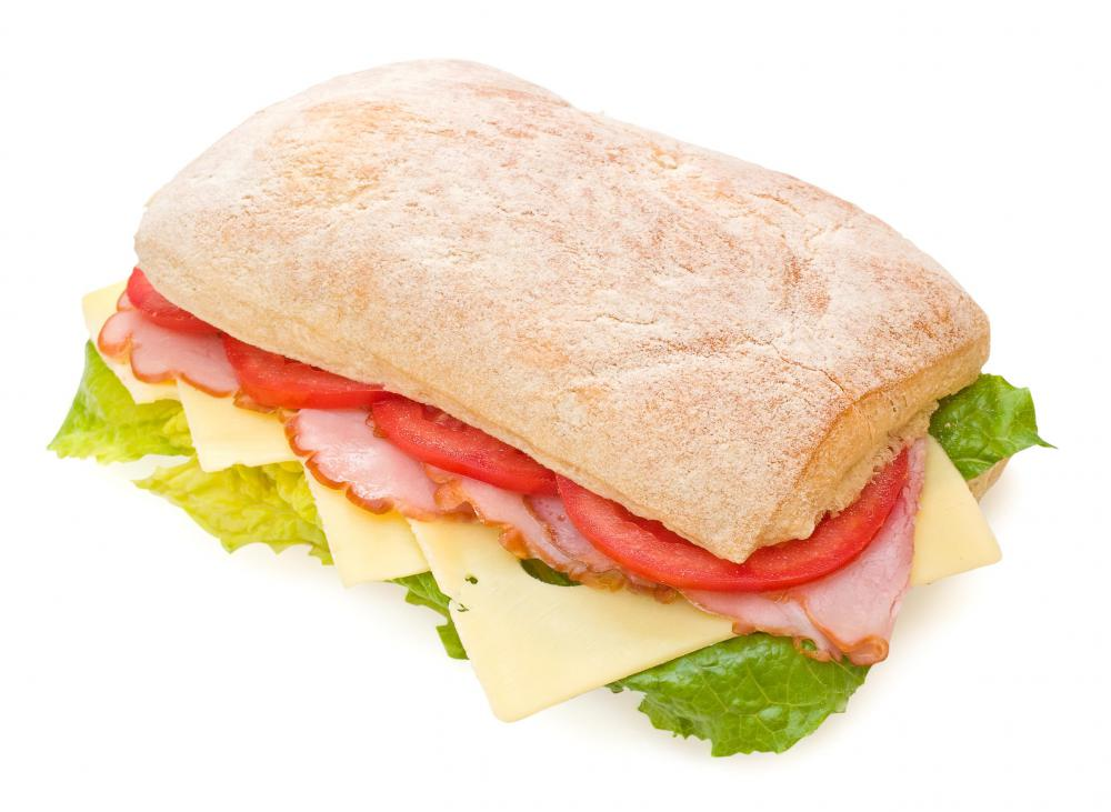 Sandwich made with ciabatta bread, ham, tomatoes, lettuce, and Swiss cheese.