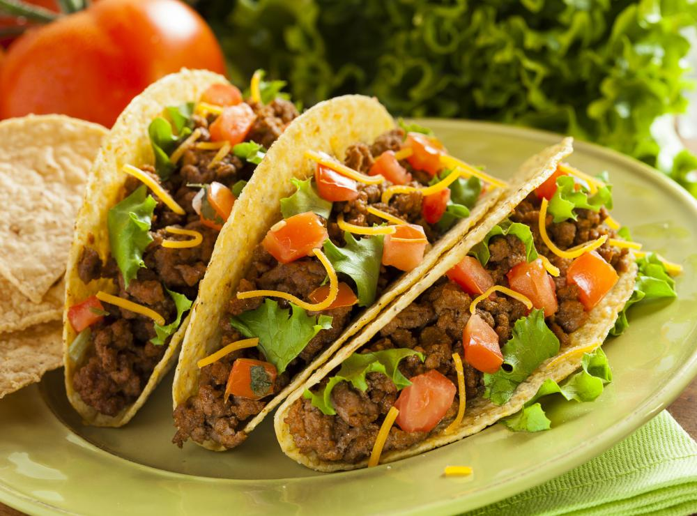 Tacos often contain beef, tomatoes, lettuce, and cheese.