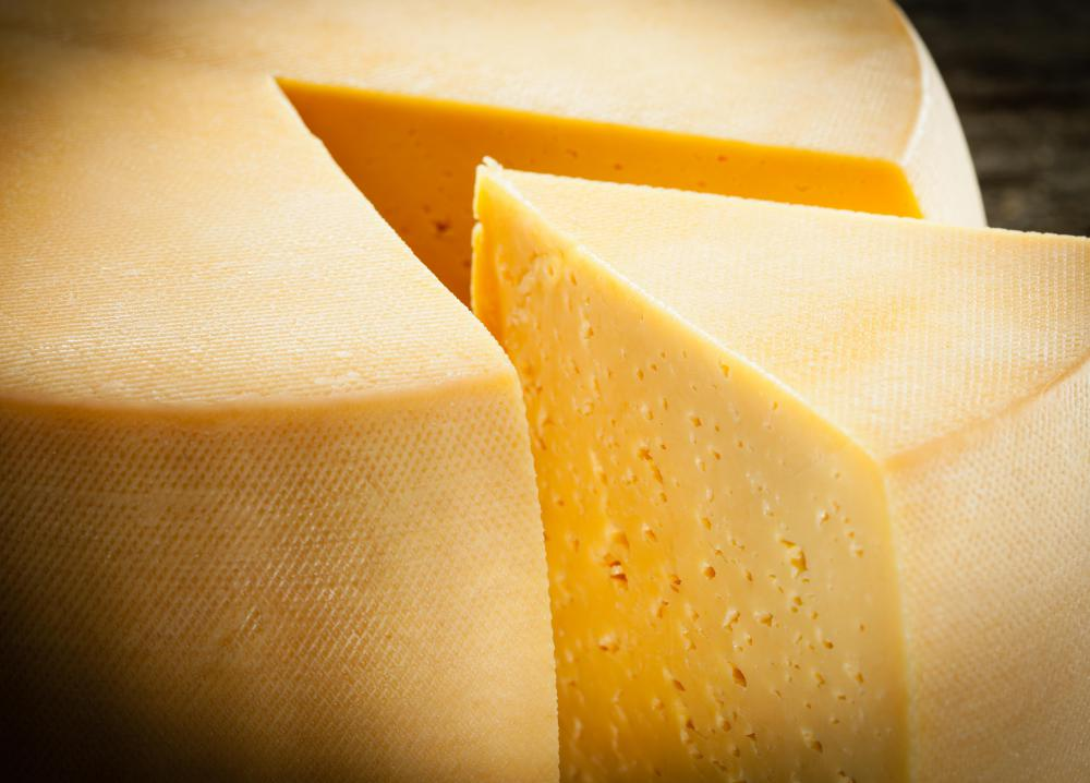 Fermenting bacteria creates bubbles in ripening cheese, leading to holes.